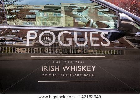 Logo of Irish whiskey The Pogues on a car. Dublin, Ireland - April 21, 2016: Logo of Irish whiskey The Pogues on the side of a black car. The official Irish whiskey of the legendary band, the Pogues.