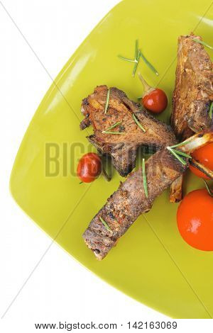 served entree: ribs on plate with hot peppers and capers on green