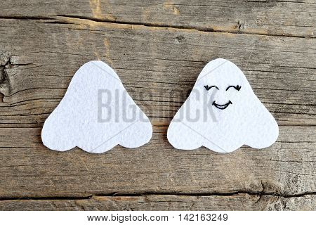 Cut from white felt details for making Halloween ghost doll. On one side embroidered with black thread eyes and mouth. Step. How to sew a cute ornament. Step by step tutorial. Old wooden background