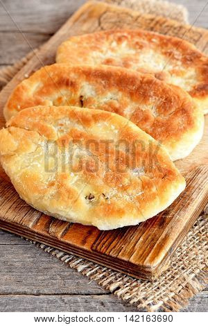 Delicious cakes cooked of unleavened dough and fried in vegetable oil in a frying pan. Pies on a cutting board. Old wooden background. Closeup