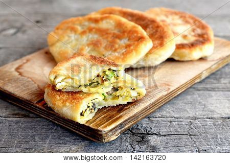 Fried cakes stuffed with mushrooms, hard-boiled eggs, green onions and dill on a wooden board. Delicious breakfast, picnic, snack idea. Unleavened dough recipe