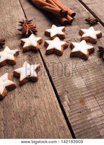 Christmas bakery with cinnamon stars on an old wooden table with cinnamon sticks and star anise