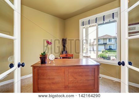 Home Office Interior With Wooden Desk And A Window.