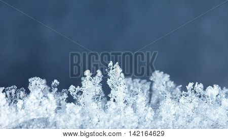 Micro of hoarfrost crystals over dark blue background
