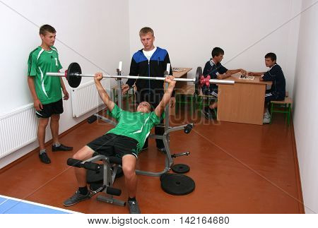 MULCHYCI UKRAINE - September 04 2012: Teenager is working out chest with barbell in a school gym during physical education classes