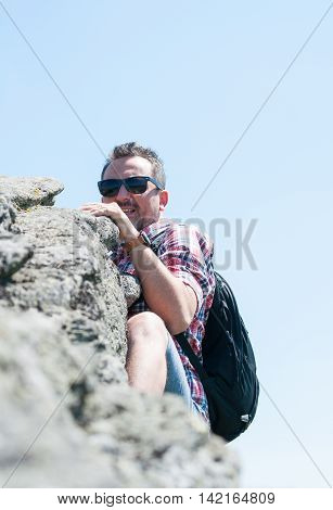 Mountaineer Climbing A Cliff On Top Of The Mountain