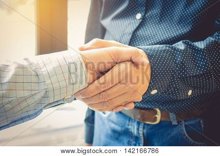 two cheerful businessman handshaking in office. vintage effect.