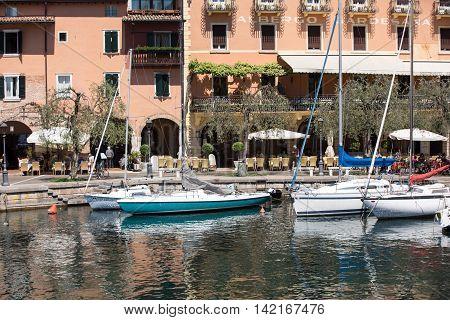 TORRI DEL BENACO - MAY 4, 2016: boats in the small harbor of Torri del Benaco. Garda Lake. Italy