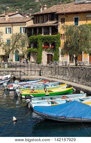 TORRI DEL BENACO - MAY 4, 2016: Fishing boats in the small harbor of Torri del Benaco. Garda Lake. Italy