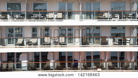 cruise ship with chairs and tables has glass windows and handrail of residential building with nobody sunny day on exterior background