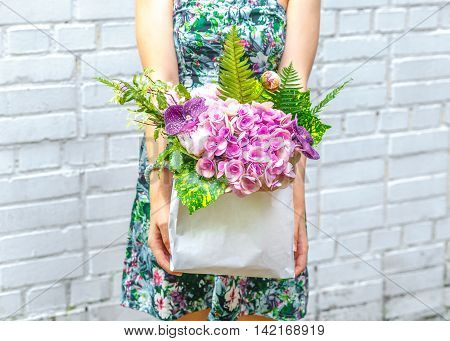 woman with bouquet of purple flowers in kraft bag on background of a brick wall