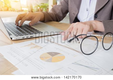 Business woman working at the office. analysis document and using laptop