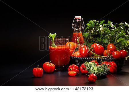 fresh organic tomatoes and tomato juice on black. the detox concept