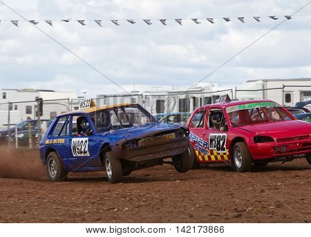 BREDON HILL, UK - MAY 4: Unnamed drivers competing in the UKAC autograss series accelerate out of the bottom corner of the oval circuit side by side on May 4, 2013 in Bredon Hill.