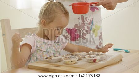 Child interested in sugar falling on baked muffins