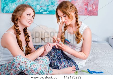 Positive Young Girl Having Fun At Home Sitting On The Bed And Pa