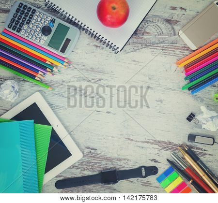 back to school hero header with school supplies on wooden table, copy space on wooden table, retro toned