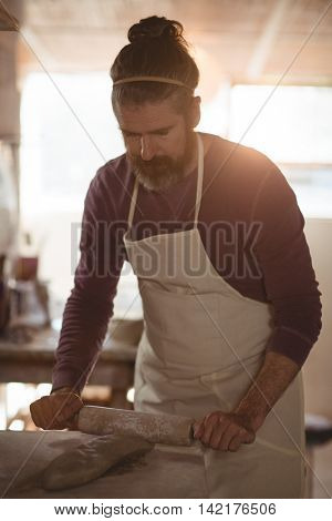 Male potter molding clay with rolling pin in pottery workshop