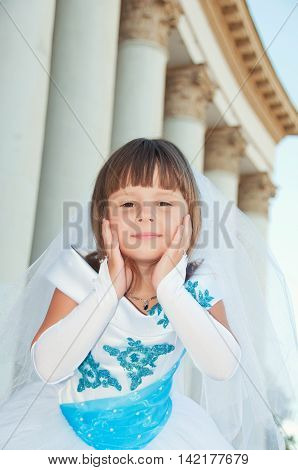 Portrait of a girl of 6 years in the lush smart dress near white columns