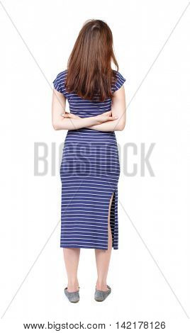 back view of standing young beautiful  woman.  girl  watching. Rear view people collection.  backside view of person. The brunette in a blue striped dress standing with his arms crossed on his back.