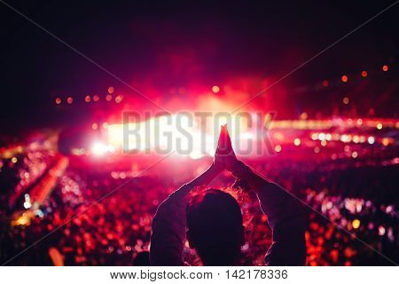Silhouette of a young woman enjoying festival lights and concert. Woman making hand gestures at concert