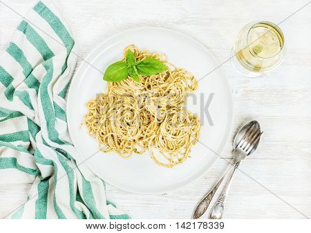 Pasta spaghetti with Pesto sauce and fresh basil served with glass of white wine. White wooden painted background, top view, horizontal composition