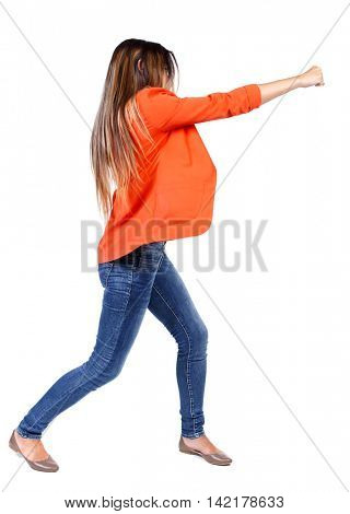 back view of woman funny fights waving his arms and legs. Rear view people collection. backside view of person.  Isolated over white background. business woman in a red jacket hand strikes.