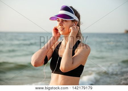 Runner girl wearing earphones and running armband phone arm strap getting ready for run workout