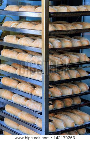 Tall metal shelf unit with freshly baked loaves of bread cooling off  on them outside in the fresh air.