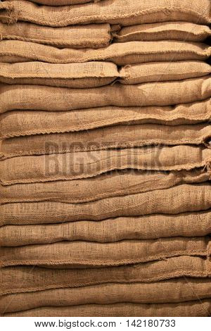 Background of burlap sandbags stacked on top of each other.