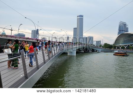 People Walking To Visit Merlion Statues On Jubilee Bridge