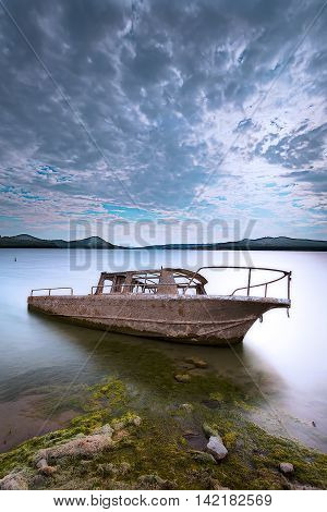 Sunken boat in the lake in a cloudy day