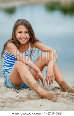 Girl In A Striped Vest On The Sand
