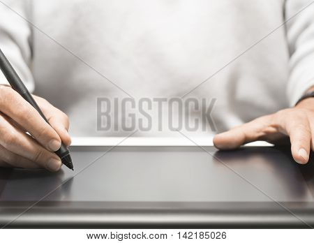 Close up of the hand of a graphic designer holding an electronic stylus. Background with free space for text horizontal image