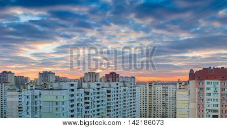 Panorama of a sunset over the housing estate with modern multi-storey apartment buildings in a big city
