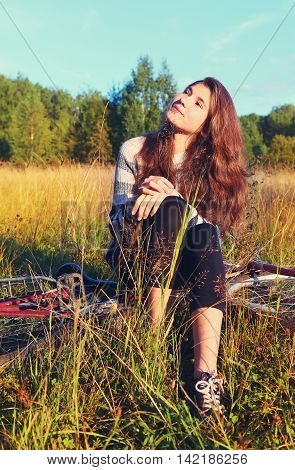 teen pretty girl with long dark brown hair sit on bicycle in the summer sunny field have break sunbathing face close up portrait