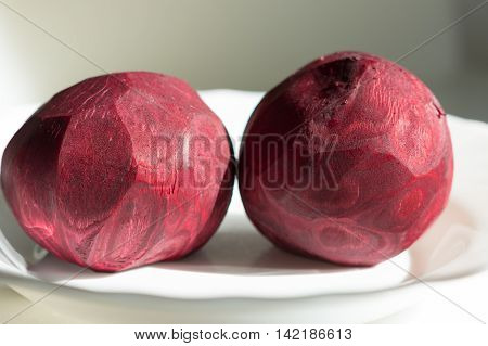 Two peeled beets that lying on the white plate. Their patterns are like some space bodys.