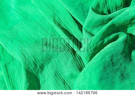 Green fabric abstract background. Chiffon cloth texture