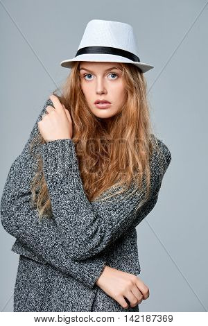 Fashionable beautiful woman in warm knitted cardigan, over gray background