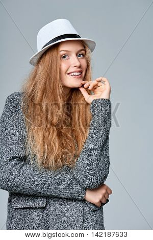 Happy smiling beautiful woman in warm knitted cardigan with hand on chin, over gray background