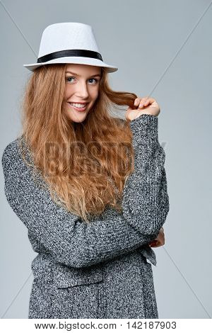 Happy smiling beautiful woman in warm knitted cardigan playing with her hair, over gray background