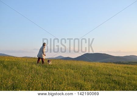 Woman with her Cavalier King Charles Spaniel Blenheim dog in a wonderful mountain landscape