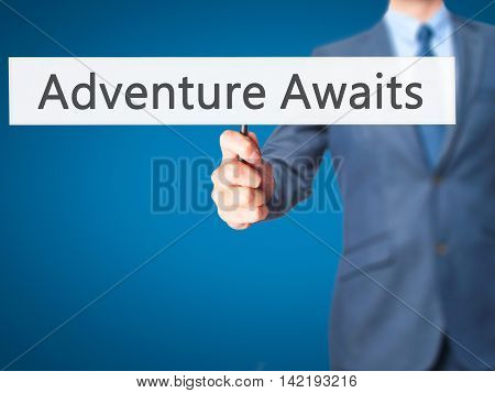 Adventure Awaits - Businessman Hand Holding Sign