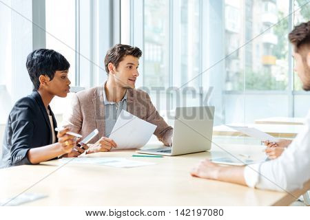 Group of young businesspeople working together in conference room