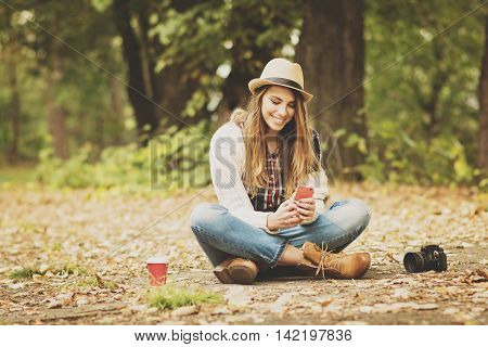 Cheerful young blonde Caucasian millennial woman sitting on leaves in park in autumn using smart phone, smiling, wearing casual fashion clothes. Matte filter applied, medium retouch.