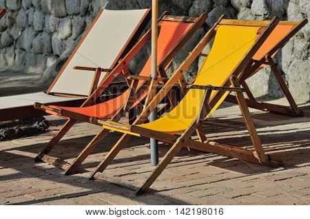 Orange and yellow sunbeds at sunset times in Italy