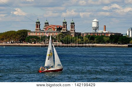 New York City: Mount Gay Barbados Rum sailboat glides past the great immigration hall on Ellis Island in New York harbor