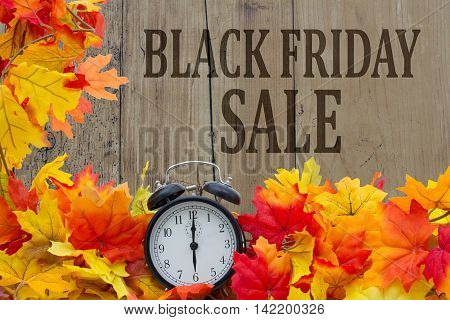 Time for Black Friday Shopping Sale Autumn Leaves and Alarm Clock with grunge wood with text Black Friday Sale