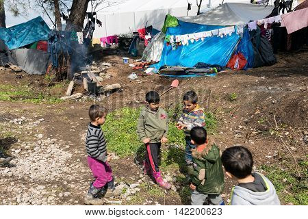 IDOMENI, GREECE - MARCH 17, 2016: Boys play near their tents on March 17 2015 in the refugee camp of Idomeni Greece. For several weeks more than 10.000 refugees and immigrants wait here for the borders to open.