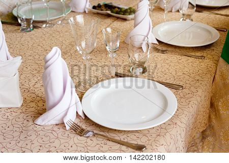 Empty white plates with napkins vineglasses forks knives closeup Cutlery on the banquet table in restaurant